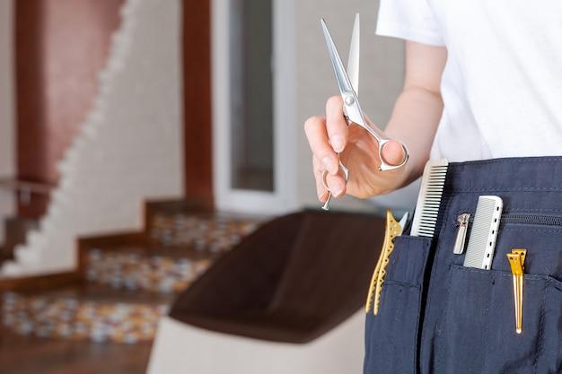 Ciseaux de coupe de cheveux dans la main de coiffeurs dans un salon de beauté, salon de coiffure intérieur de studio de beauté. outils de coiffeur professionnel.