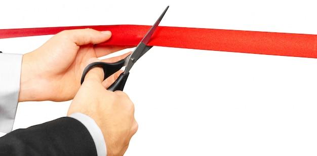 Des ciseaux coupent un ruban rouge ou du ruban adhésif