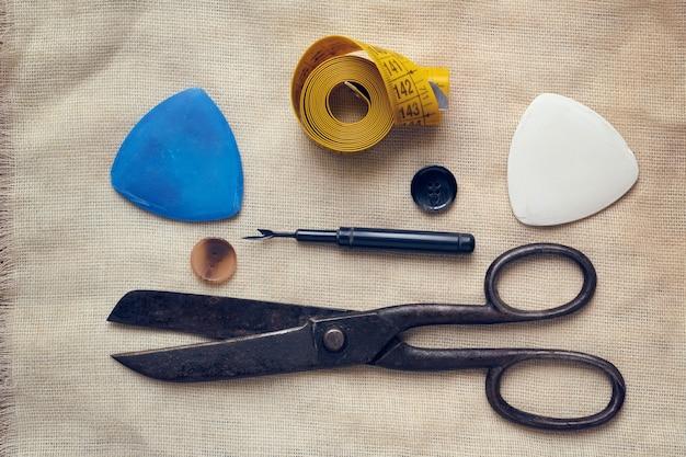 Ciseaux, craie, ruban à mesurer, boutons, pose à plat