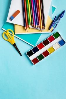 Ciseaux, diviseurs, crayons, cahiers et aquarelles sur bleu avec espace de copie.