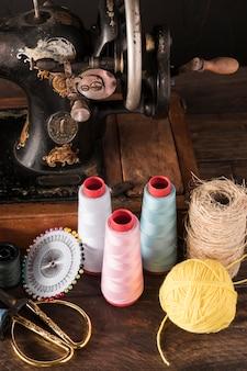 Ciseaux et épingles près des fils et de la machine à coudre