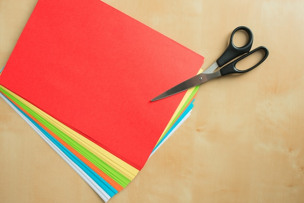 Ciseaux et feuilles de papier de couleur sur la surface en bois de la table