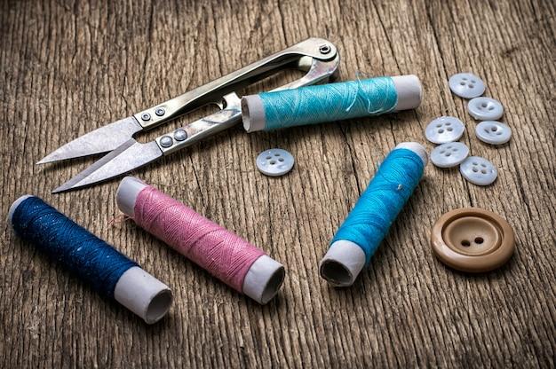 Ciseaux, fil et boutons sur fond de darianna inaudible dans un style vintage
