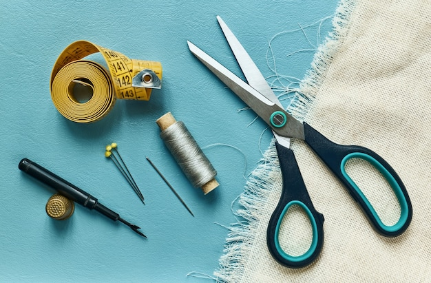 Ciseaux, mesure, filetage, dé à coudre et épingles sur la surface bleue, vue du dessus