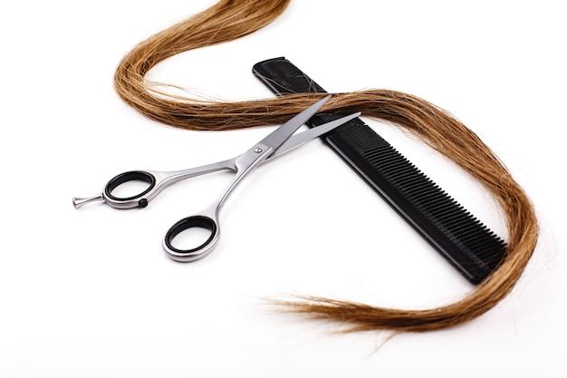 Ciseaux et peignes pour la coupe de cheveux et le traitement se trouvent sur une table blanche