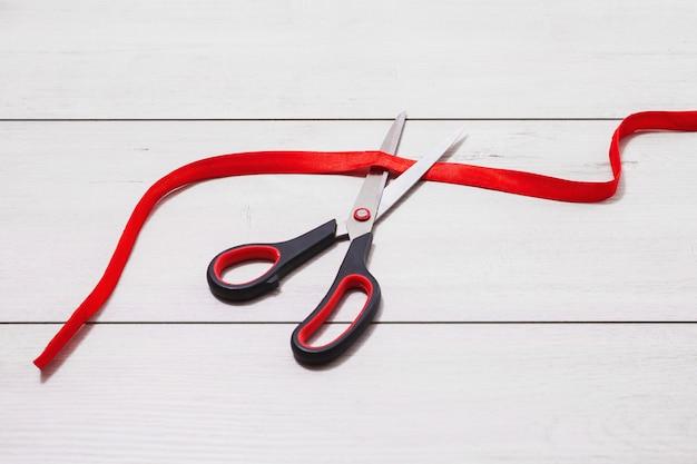 Des ciseaux avec des poignées rouges coupent le ruban rouge. la paperasserie est couchée sur fond en bois.