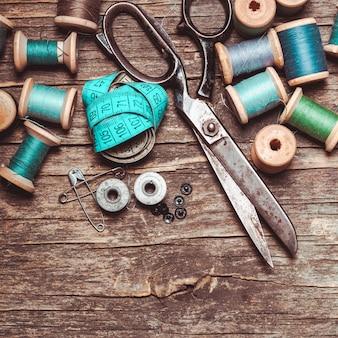 Ciseaux rétro, textiles et fils à coudre sur la table en bois