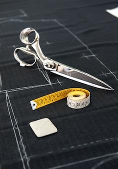 Ciseaux et ruban à mesurer sur le tissu dans studio