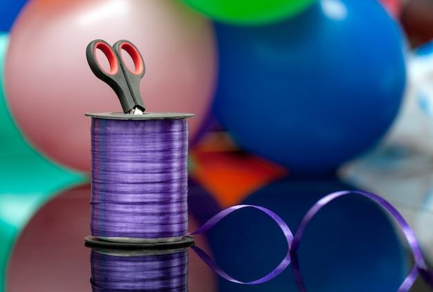 Ciseaux et ruban washi violet sur fond flou de ballons multicolores.