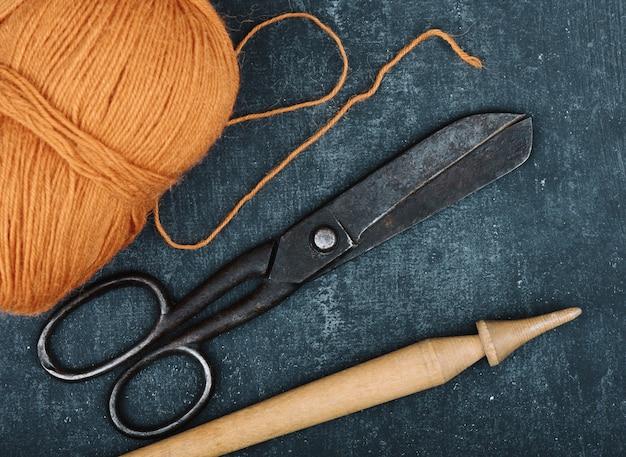 Ciseaux de tailleur rouillés antiques, enchevêtrement de fil de laine de couleur orange et broche sur fond gris, gros plan