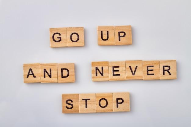 Citation de motivation et d'inspiration. montez et ne vous arrêtez jamais. blocs en bois isolés sur fond blanc.