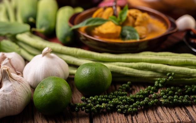 Citron, ail, haricots longs et graines de poivre frais sur une table en bois