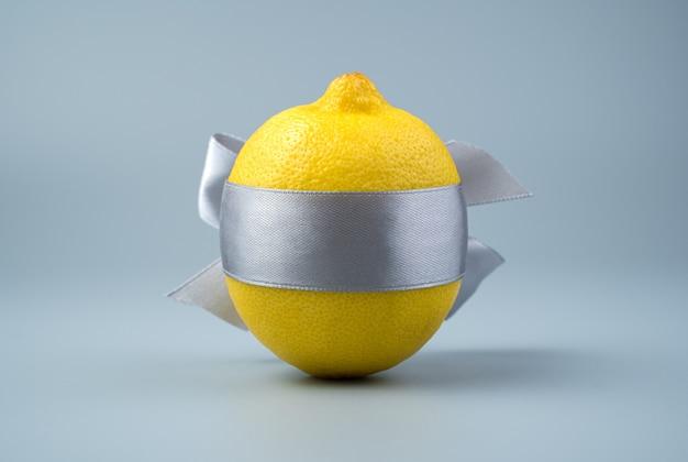 Citron attaché avec un ruban sur fond gris.