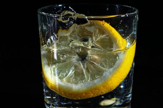 Citron dans un verre d'eau sur fond noir foncé