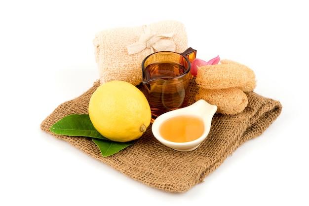Citron avec du miel et de l'eau isolé sur blanc