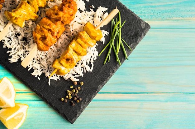 Citron et épices près de la planche avec brochette de poulet