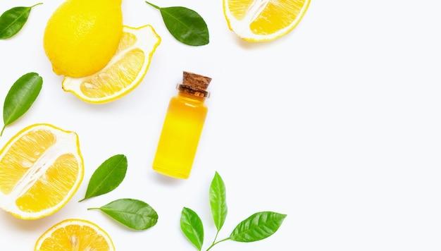 Citron frais avec bouteille d'huile essentielle sur fond blanc.