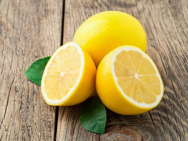 Citron frais et coupé à moitié sur une vieille table en bois, vue latérale
