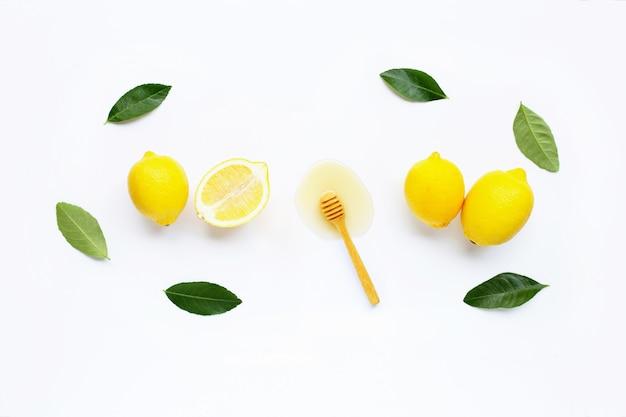 Citron frais avec du miel sur blanc