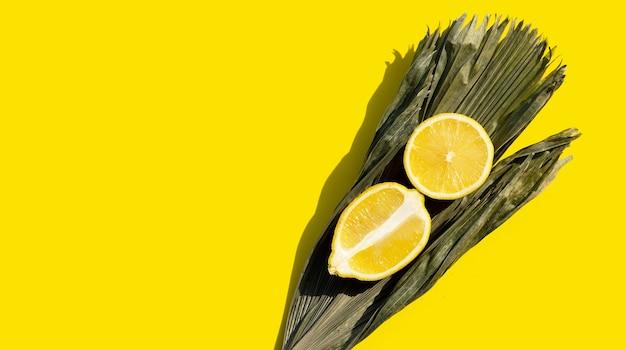 Citron frais avec feuille sèche de palmier sur surface jaune