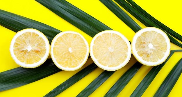 Citron frais avec feuille verte sur fond jaune.