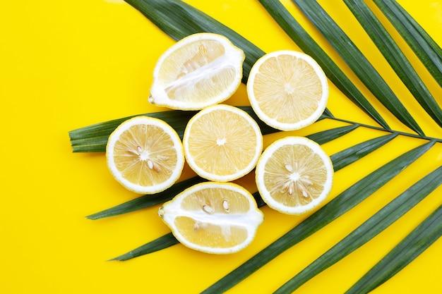 Citron frais sur des feuilles de palmiers tropicaux sur fond jaune.