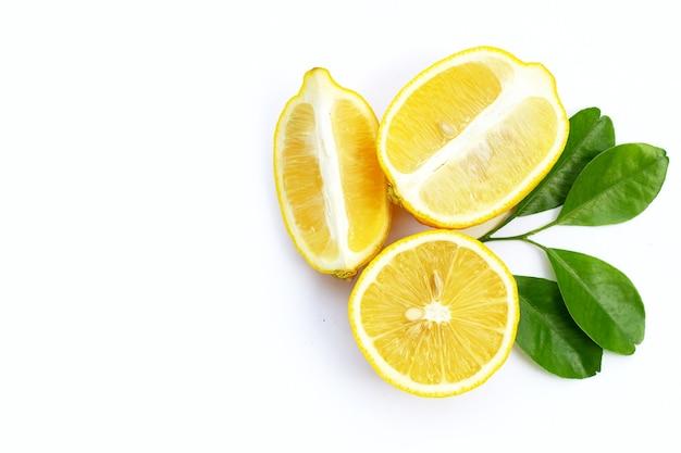Citron frais avec des feuilles vertes sur fond blanc.