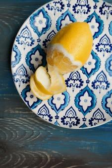 Citron frais jaune sur la plaque orient avec motif bleu sur fond de bois