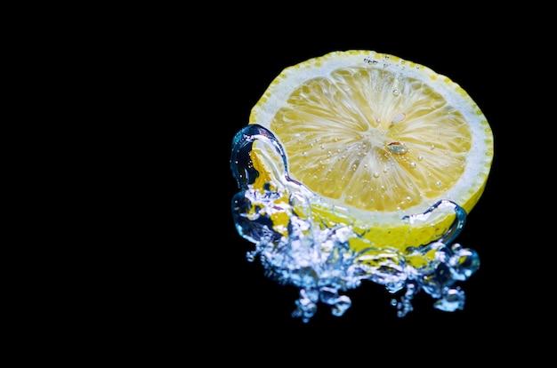 Citron frais tombant dans l'eau avec des éclaboussures sur fond noir
