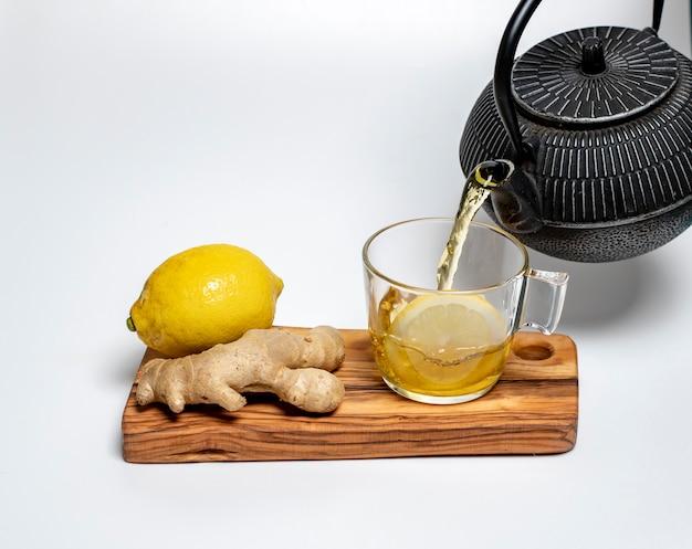 Citron, gingembre et une tasse de thé au citron sur une planche d'olive sur fond blanc