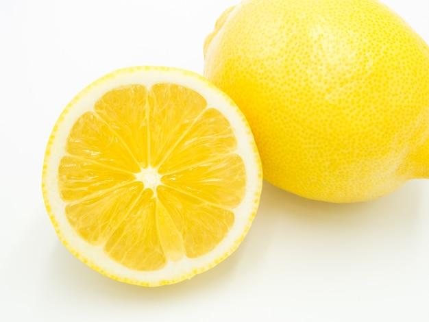 Citron jaune coupé en deux et plein sur fond blanc.