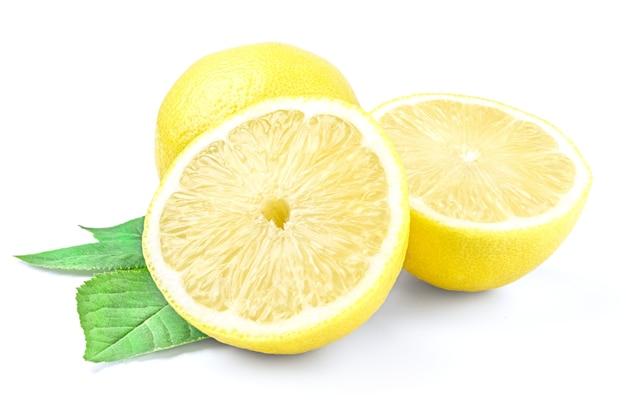 Citron jaune et deux moitiés isolés sur une surface blanche avec feuille verte