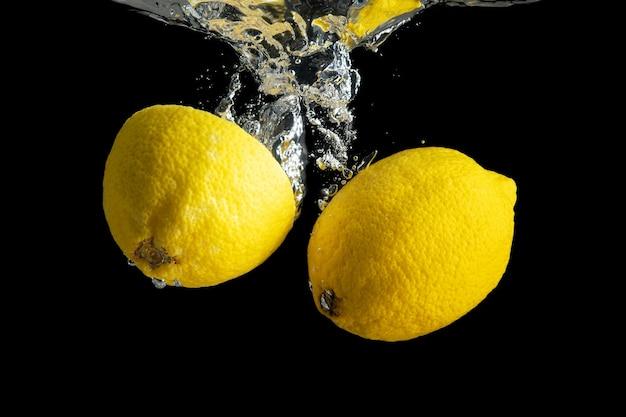 Citron jaune frais dans les éclaboussures d'eau isolé sur fond noir.