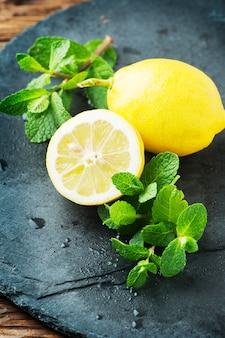 Citron jaune frais et menthe verte sur la table