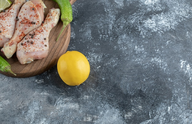 Citron jaune frais et pilons de poulet cru sur planche de bois.