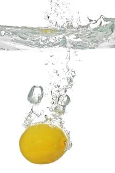 Le citron juteux tombe dans l'eau