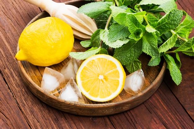 Citron, menthe, glace dans un plateau en bois sur un fond en bois