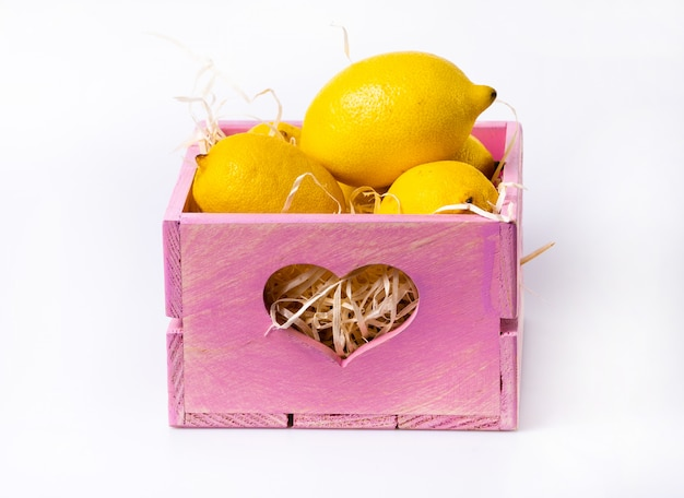 Citron mûr dans une boîte en bois isolé sur blanc