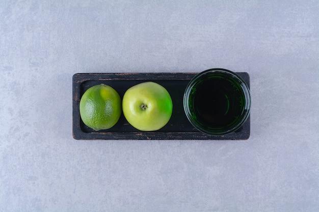 Citron, pomme et jus de pomme sur une assiette en bois, sur la table en marbre.
