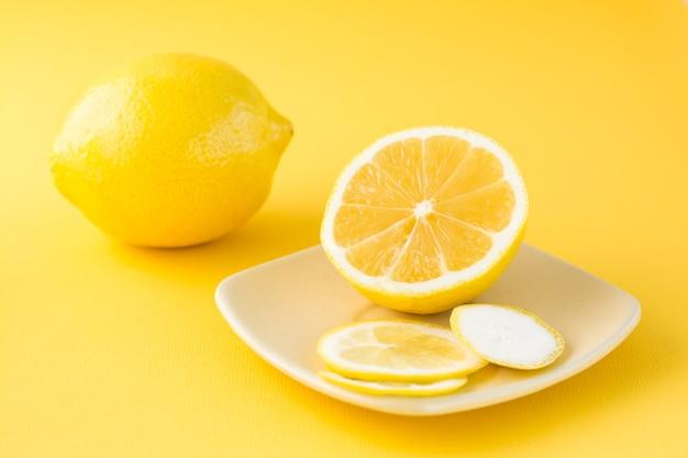 Citron tranché sur une soucoupe et un citron entier à côté sur une table jaune.