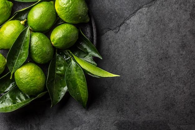 Citron vert citron vert avec des feuilles fraîches sur une plaque noire, fond ardoise