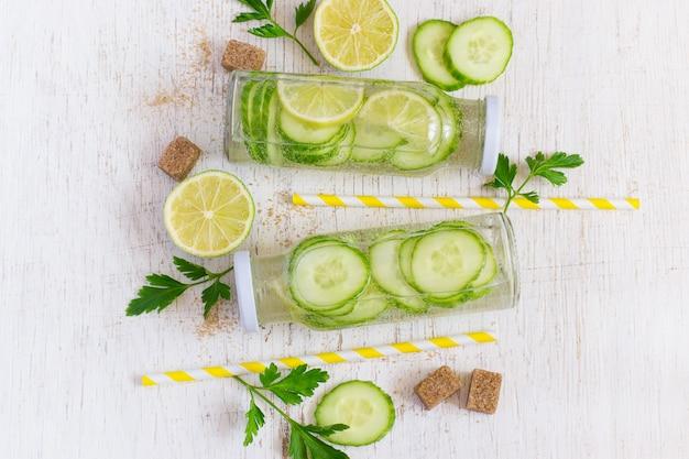 Citron vert, concombre, limonade au persil dans des bouteilles sur un fond blanc