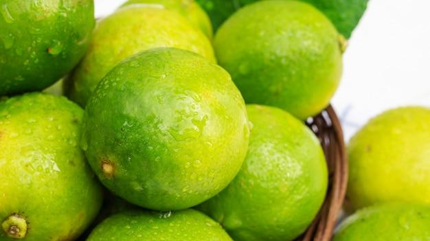 Citron vert dans un panier sur une table en bois blanche.
