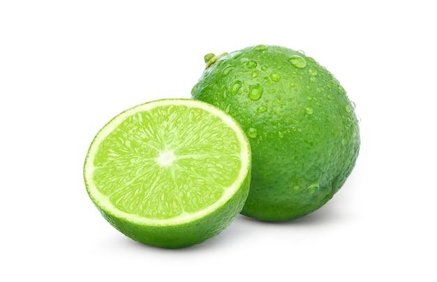 Citron vert frais avec des gouttelettes d'eau et de tranches isolées sur blanc