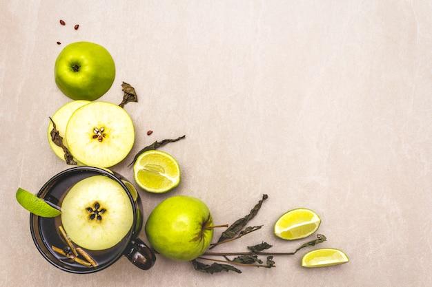 Citron vert frais et pomme, tasse de thé et herbes sèches