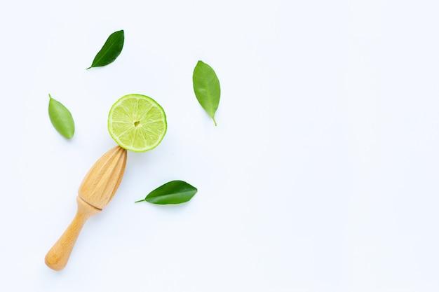 Citron vert frais avec presse-agrumes en bois blanc