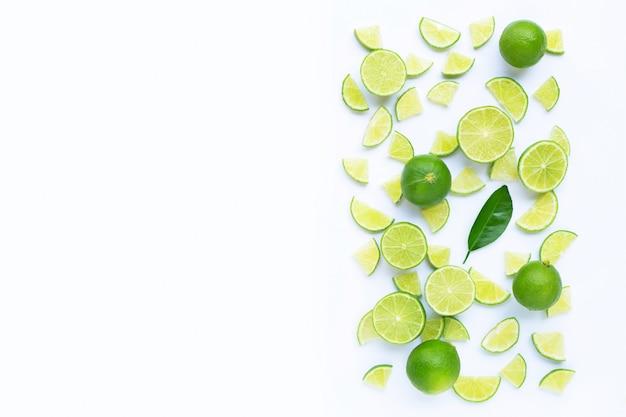 Citron vert frais avec des tranches isolés sur fond blanc.