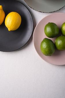Citron vert et fruits aigres dans des assiettes colorées sur blanc