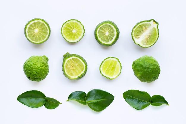 Citron vert kaffir frais ou fruit de bergamote avec des feuilles isolées sur blanc