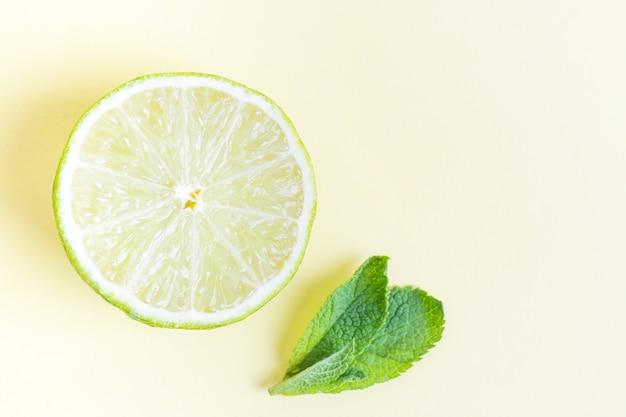 Citron vert et menthe feuilles sur un jaune pastel.